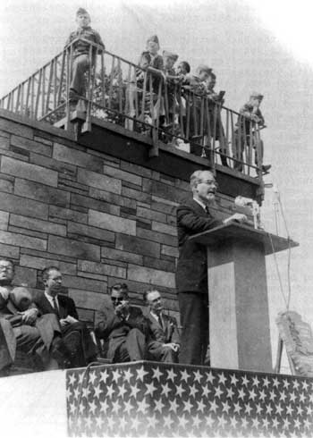 A man speaks at a podium with children on the building roof looking down
