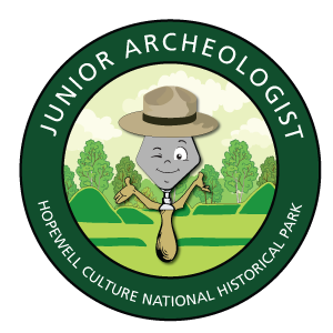 A caricature trowel winking inside of a green circle that reads Junior Archeologist