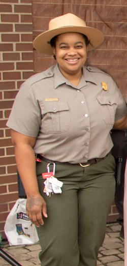 A ranger in a tan flat hat, grey shirt and green pants