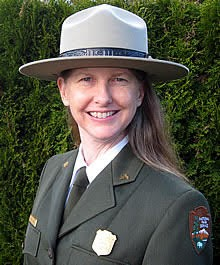 A portrait of a woman in a flat hat and green jacket