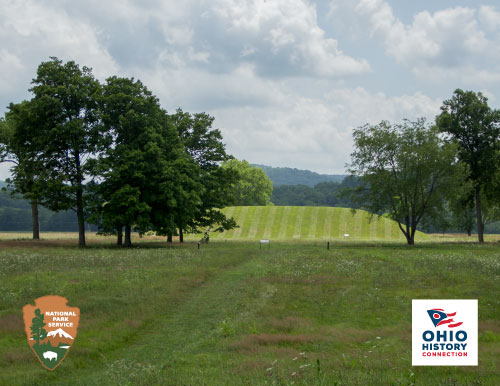 Grass-covered mound of dirt in background with trees surrounding the mound, NPS arrowhead and OHC logo in foreground.