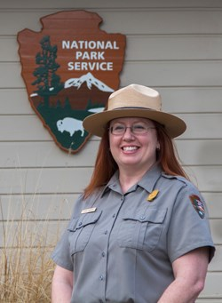 A ranger wearing a flat hat and standing in front of the NPS arrowhead