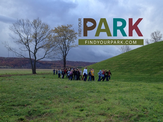 Students walk around Seip Mound with the Find Your Park logo atop the photo.