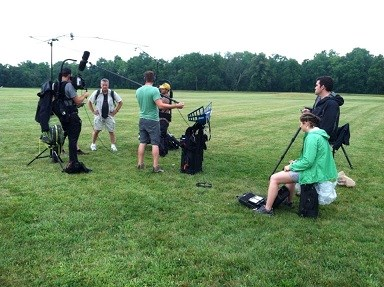 Several people on a grassy field holding video equipment and watching people being interviewed