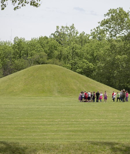 Kids walk in front of a large mound in a grassy field