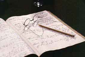 An historic ledger with eyeglasses and pencil resting on an open page.