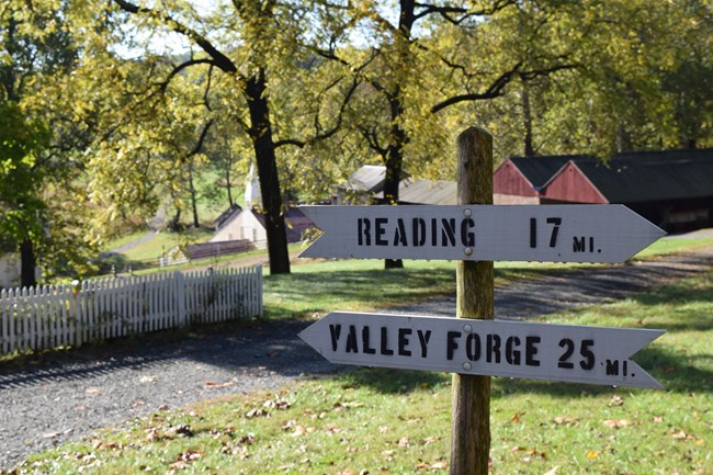 Wooden sign with directional arrows and mileage to Reading and Valley Forge.