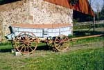Conestoga wagon with the typical blue painted body and red wheels.