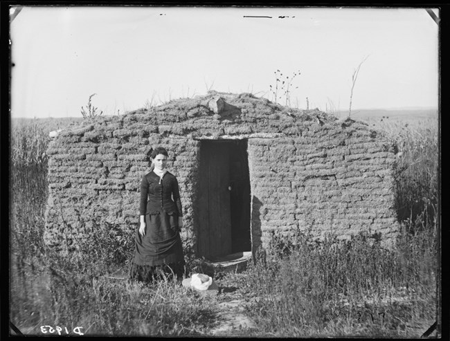 Woman standing in front of a sod house