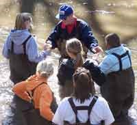 Volunteer helps students collect samples from Cub Creek.