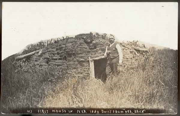Solomon Butcher standing in front oh is first Nebraska house; a sod house