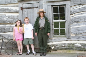 Young visitors pose with Park Ranger after making cornhusk dolls.