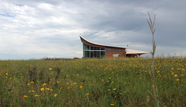The plow-shaped Heritage Center stands tall about a sunflower sea.