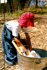 Girl dressed up as a homesteader pretending to wash clothes.