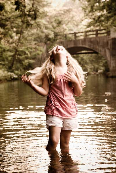 Tinted photo of a young girl with long blond hair standing in a stream; her head is back in laughter. Behind her is a bridge and treeslining the stream. The girl is wearing a pink top and white shorts.