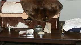 Hide-covered trunk with beaver fur laying over it and some early 1800s period items laying on table