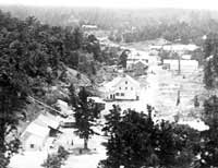 black and white photo of a valley with several buildings built on the right side of a stream with a dirt street in front. There are a fewer buildings on other side of street with some chimneys indicating former building places.