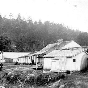 black and white photo of several wooden one story buildings that appear to be connected; they are facing a stream bank on the left.