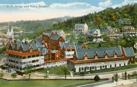 color post card image of hospital complex taken from the south at an elevated vantage point. Shows most buildings in red, as they were brick, with white veranda around some.
