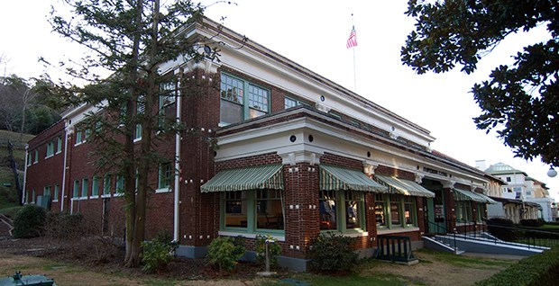 Two story, red brick Superior Bathhouse. Building has large windows on the first floor that are shaded by green and white awnings.
