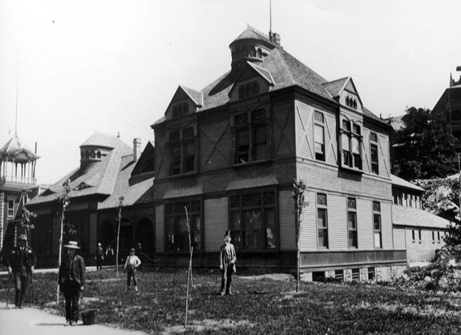 Old wooden Lamar Bathhouse in 1889 with several figures standing out front.