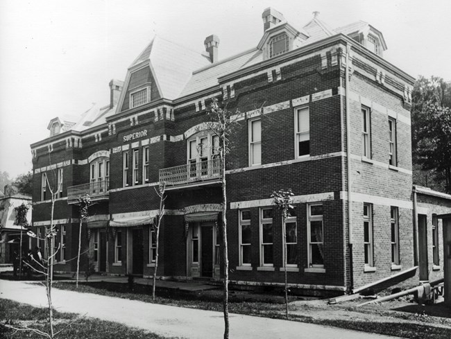 Black and white image of a two-story red brick building.
