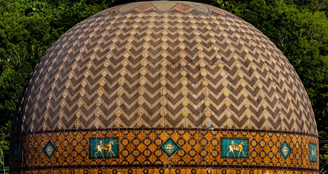 The dome roof of the Quapaw Bathhouse is an intricate pattern of mosaic tiles put together by hand. It has stripped tiles with flowers in between, leading to the top, with horses and lion faces surrounding the lower portion.