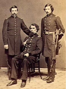 sepia tone image of three men in Union Army uniforms. One is seated with the other two flanking. All have dark hair.