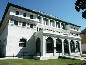 color photo of the Maurice from the north front side. It is a three story white stucco building of the California Modern style with large arched plate glass windows on all sides of the enclosed porch. Center of the roof you can see the skylight cover peaking over the top of the green tiled roof.