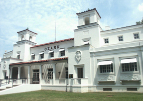 color photo of Ozark Bathhouse from the south end of the building, with the sidewalk and lawn in front. It's a sunny day with a light blue sky with a few clouds. The Ozark is a white stucco building of the Spanish Colonial Revival style of architecture with a red tile roof and open porch.