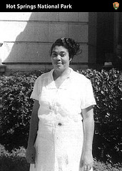 Black woman in white dress that looks like a nurses's uniform, in front of building with hedge