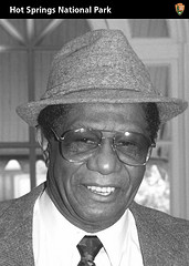 Head and shoulders shot of black man wearing a fedora style hat, suit jacket, white shirt and tie.