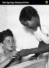Black woman giving cup to white woman sitting in a bath tub.
