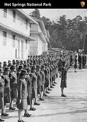 Women in uniform standing at attention in rows with a white stucco building behind them, waiting for inspection.