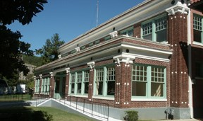 color photo of the Superior Bathhouse from the south end. It is a two-story dark red brick with many windows and the windows have a lime green trim.