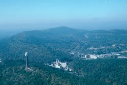aerial view of Hot Springs Mountain with the Mountain Tower on the lower left, West Mountain and Music Mountain above the tower and the valley with downtown buildings showing on the right. Photo has a blue hue.
