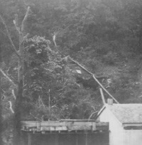 black and white 1867 photo of a wooden flume coming down the hillside to a collecting tank built to the left of the bathhouse building