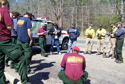 Wildland fire fighters standing around fire leader at briefing