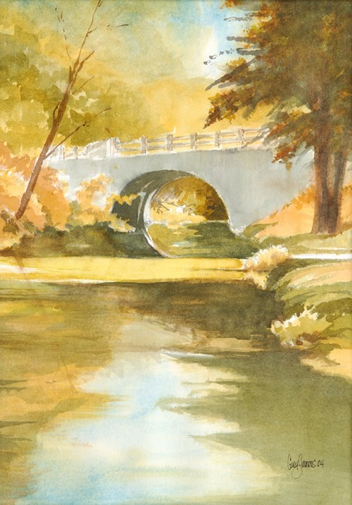 watercolor painting with creek in foreground, reflecting blue sky in center and orange leaves on left and shadows on right, center of picture is a light gray half moon bridge with trees on either side