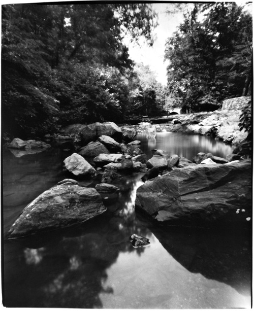 Black and white photo (taken with a pinhole camera so the edges are not square) of a Gulpha Creek looking upstream from a pool. There are large rocks flanking the creek with a small fall near the center. The artist is in the center but blurry so hard to see. Trees close in in the background.