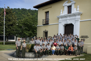 park employees, most in uniform, standing in front of adminstration building, on steps and around fountain