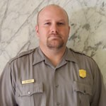 Portrait of ranger in uniform: white male with light brown facial hair and very short light brown hair, solemn look