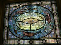 Stained glass window, a rectangle of geometric design with a ring of a naked man, naked woman and a mermaid swimming with water creatures. Colors are blues and greens primarily.