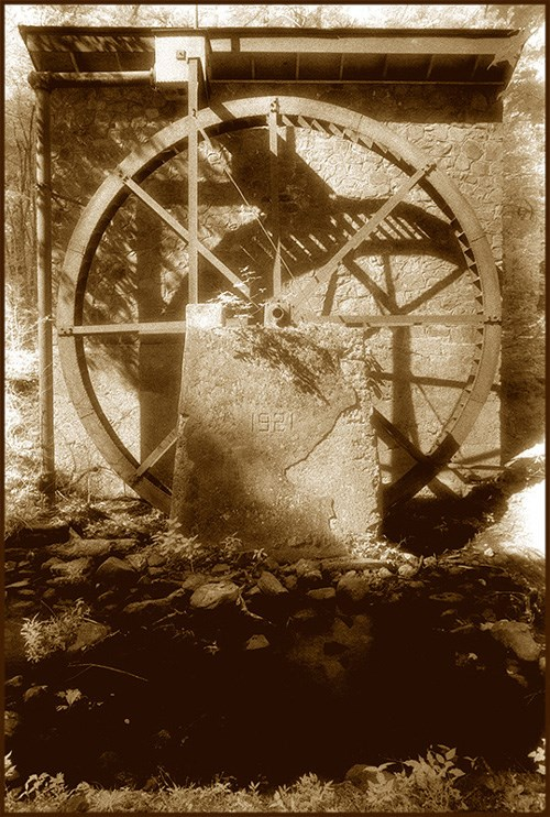 sepia tone photo of a stone structure with a large water wheel mounted on the side, shadowy foreground