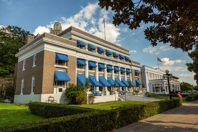 The front of the Buckstaff bathhouse on a sunny day showcasing its iconic bright blue awnings.