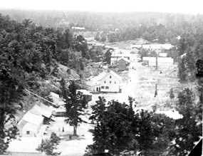 black and white photo from stereograph; looking south on the hot springs valley with mountain on left and small wooden buildings along either side of a dirt road; some foundations visible of buildings burned during the Civil War