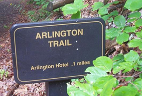 Close up view of Arlington Trail sign, a brown metal sign with gold lettering and a gold border line, surrounded on the right by leafy foliage