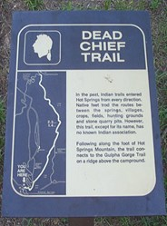 Photo of Dead Chief trailhead sign made of dark brown metal with gold lettering and map of the trail