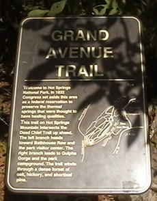 Photo of Grand Avenue trailhead sign with shadow over upper half of picture. Sign is dark brown metal with gold lettering and map of trails on Hot Springs and North Mountains