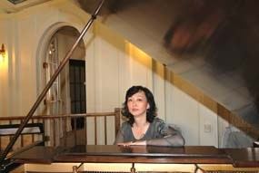 Asian woman sitting at piano, shot from across piano with lid up